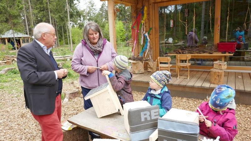 Die Kinder des Waldkindergartens spielen begeistert in und um ihr neues Blockhaus. (v. li: Helmut Rauscher, Daniela Idzik-Neumann)